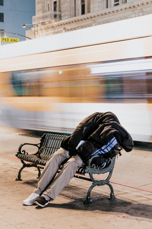person sleeping on black steel bench