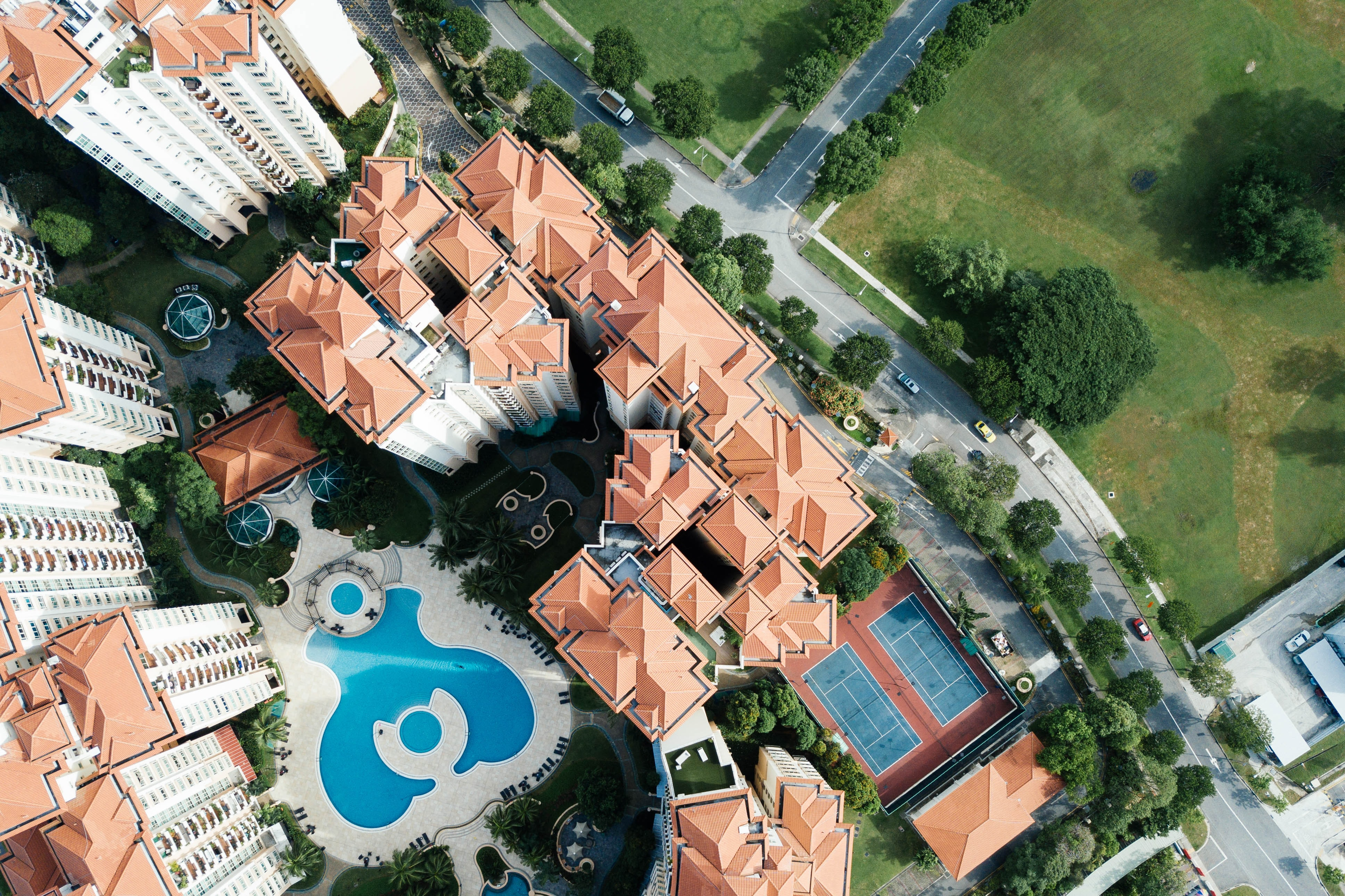 top view photography of brown-and-white buildings beside swimming pool