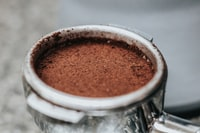 selective focus photography of coffee ground in round container