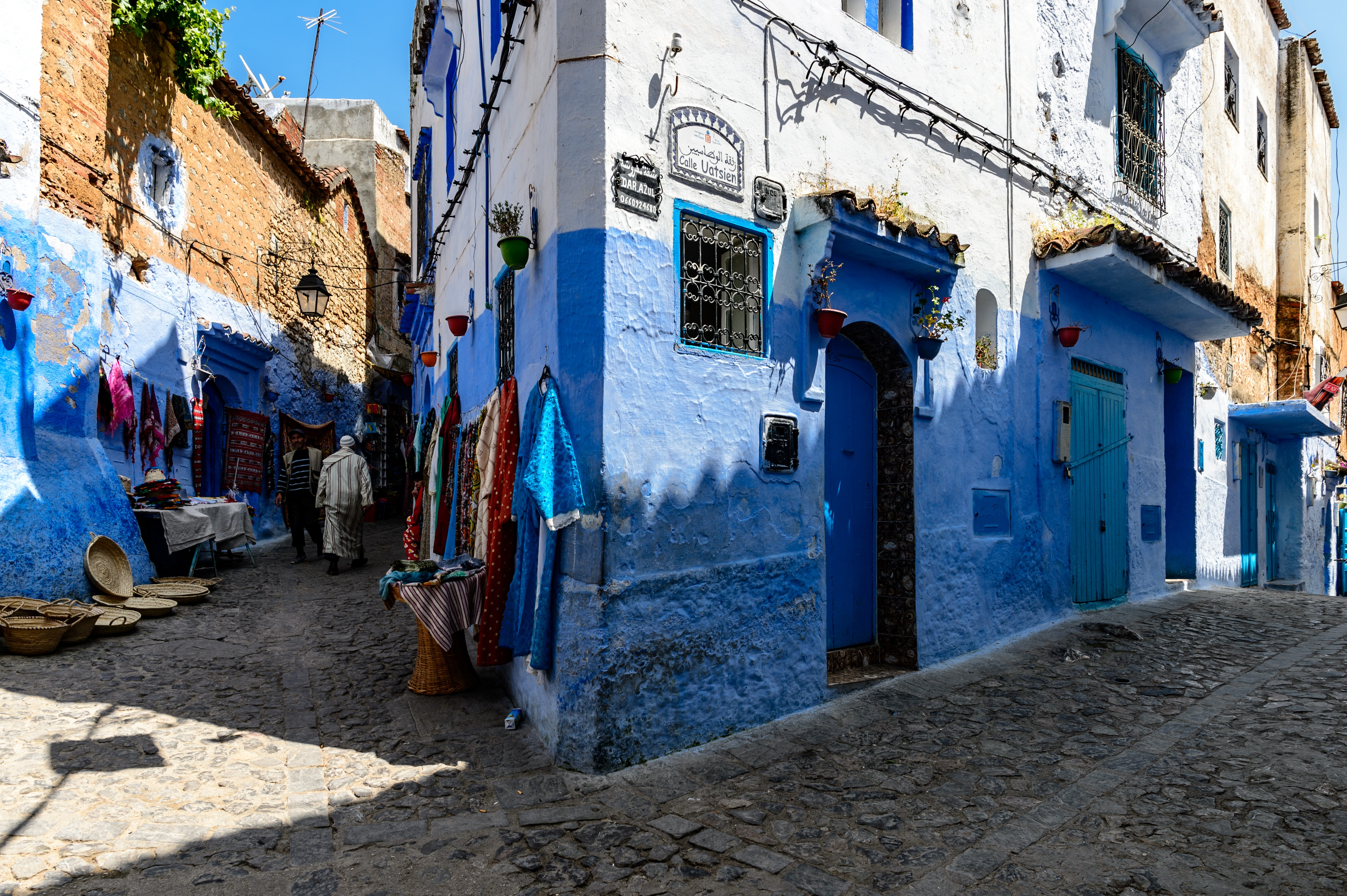two person walking in between blue and white concrete building