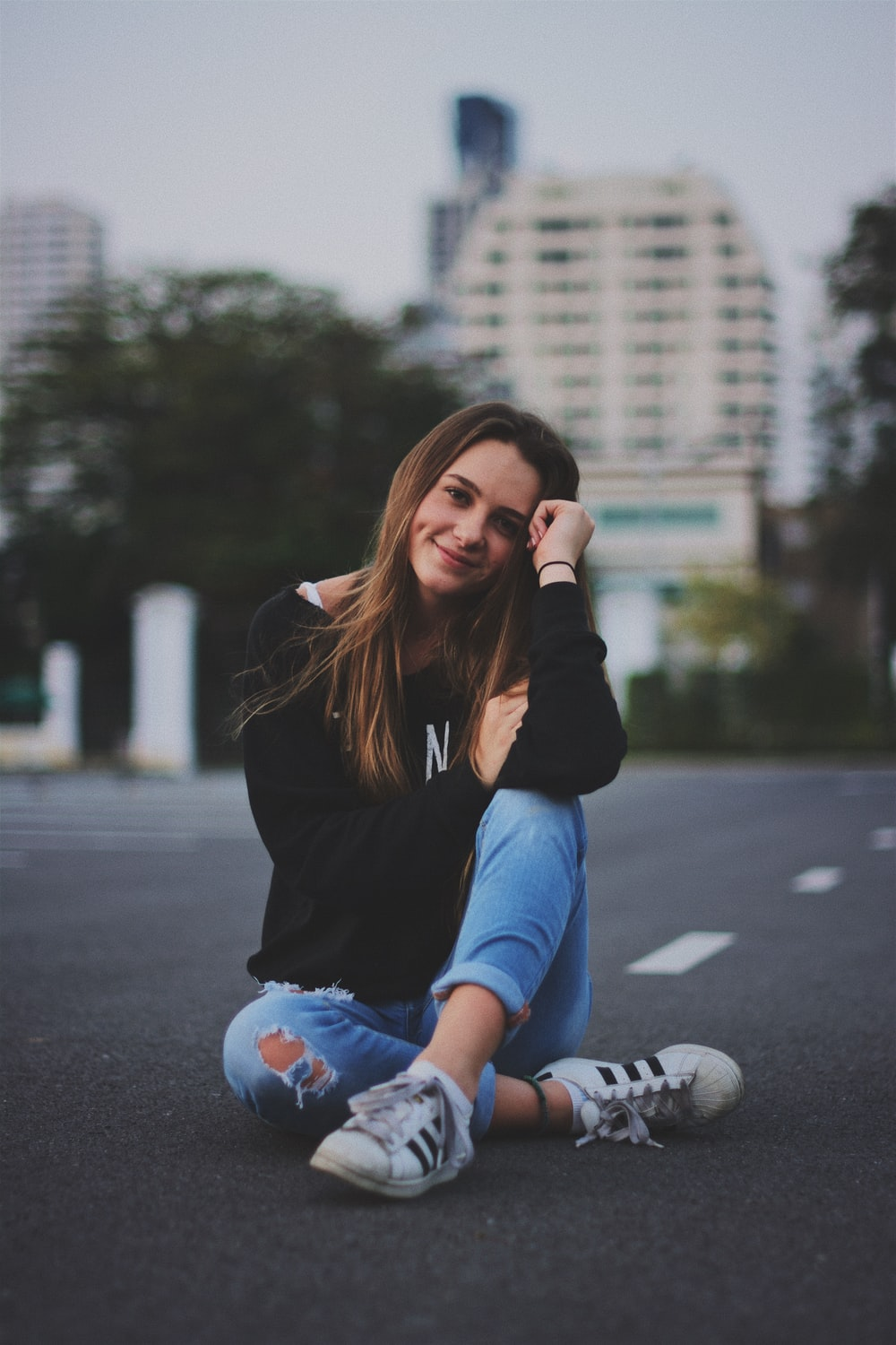 woman smiling while sitting on road with hand resting on top of her knee