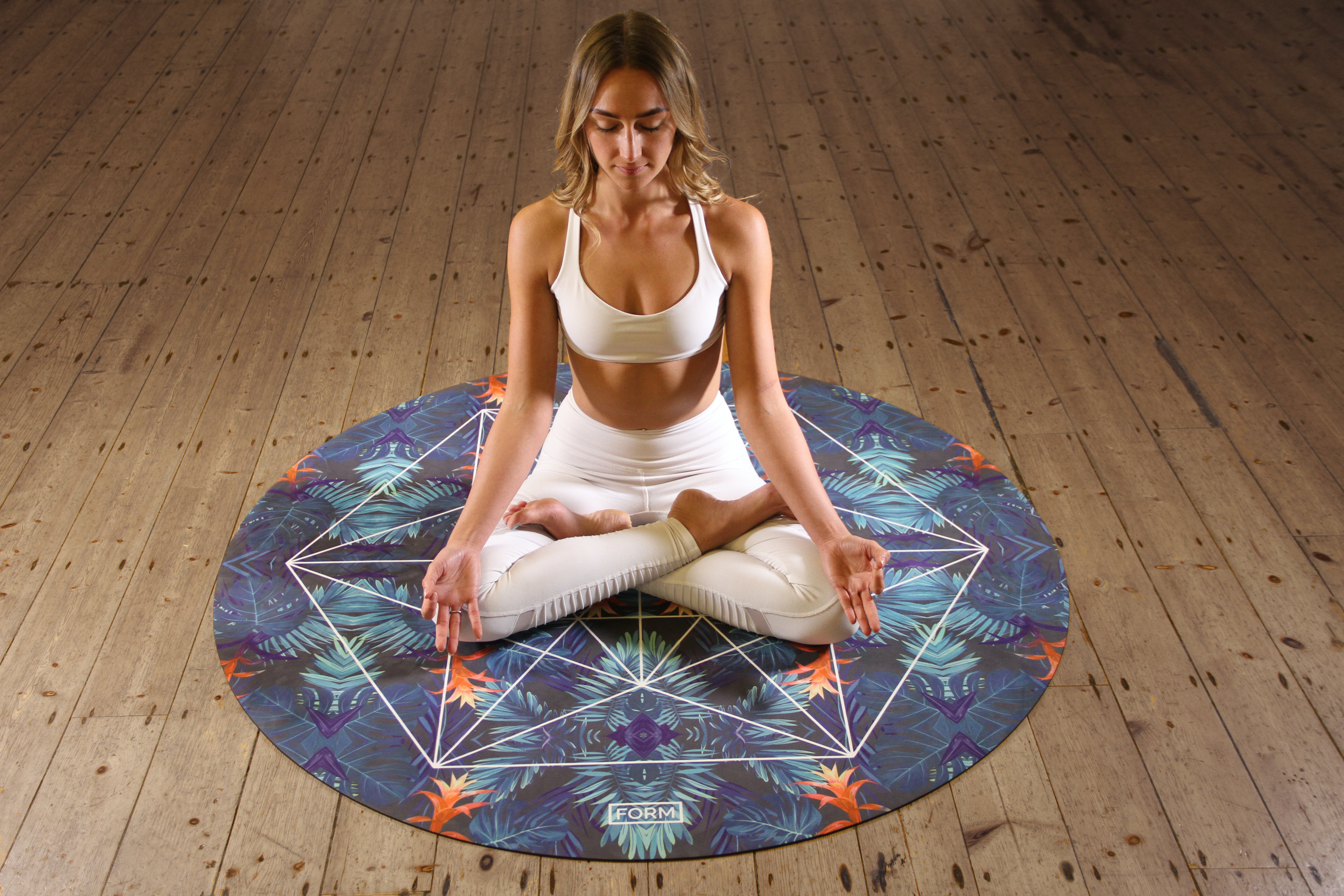woman sitting on round multicolored mat doing yoga