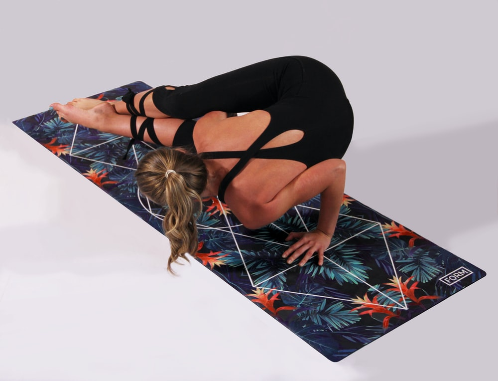 woman dosing yoga on multicolored yoga mat
