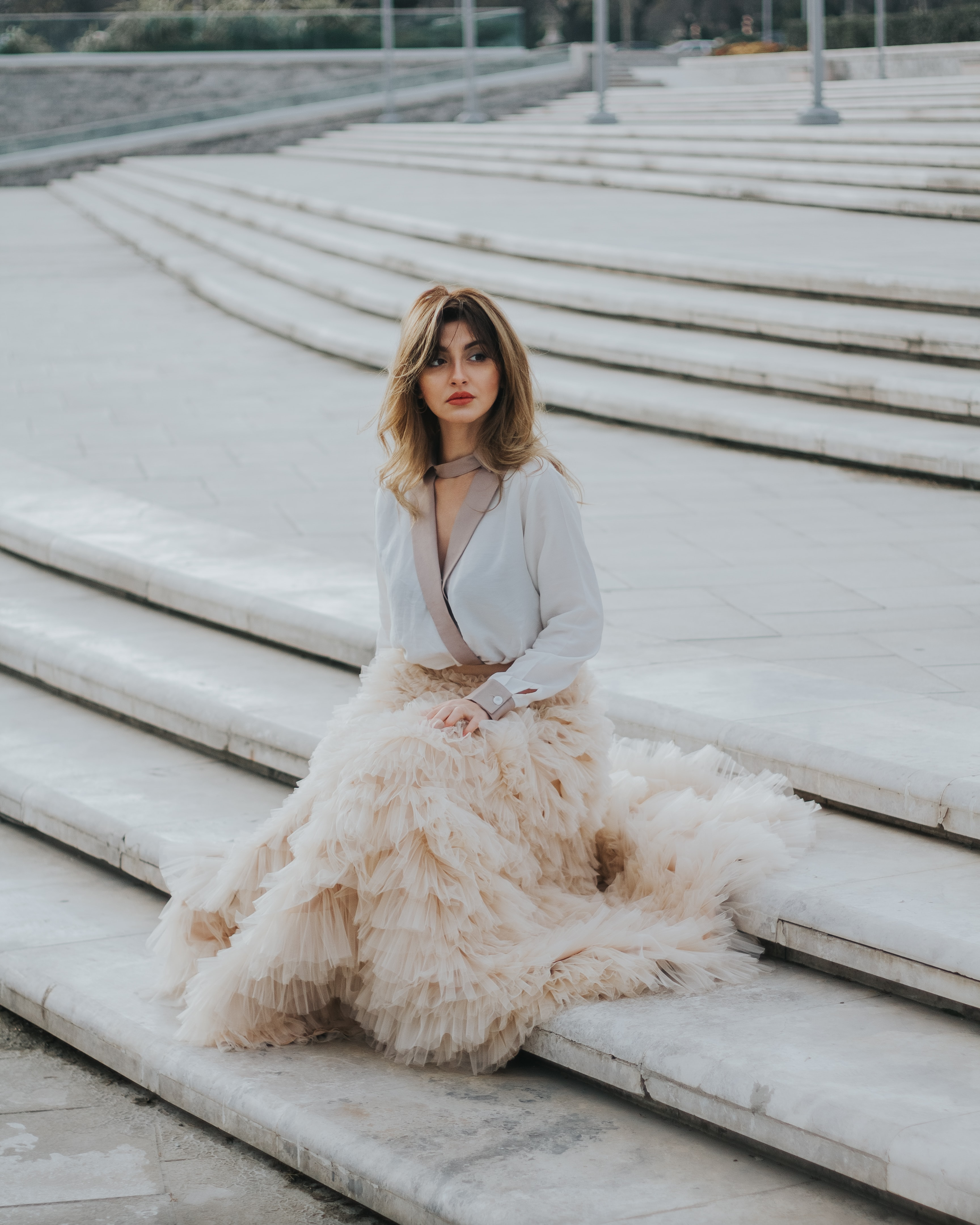 brown haired woman in white dress sitting on gray concrete stair during day time