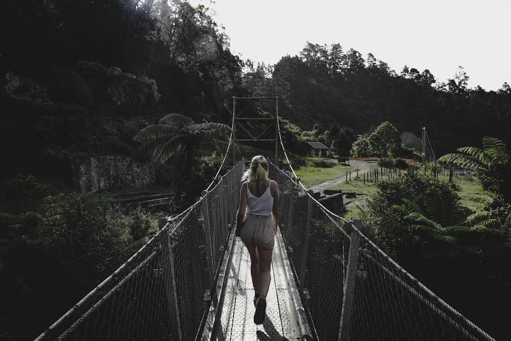 woman in white tank top waling in bridge during daytime