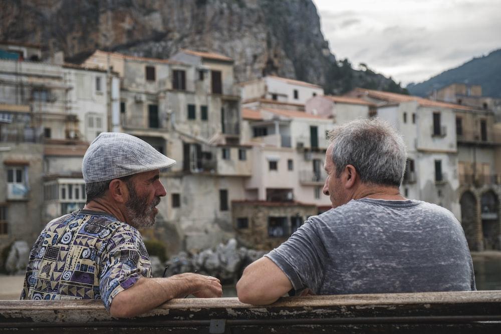 two men sitting on bench talking near village during day