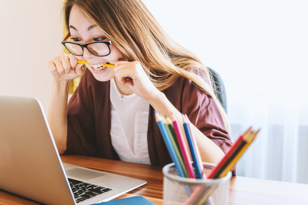 woman biting pencil while sitting on chair in front of computer during daytime