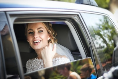 woman wearing wedding dress smiling inside car beautiful teams background