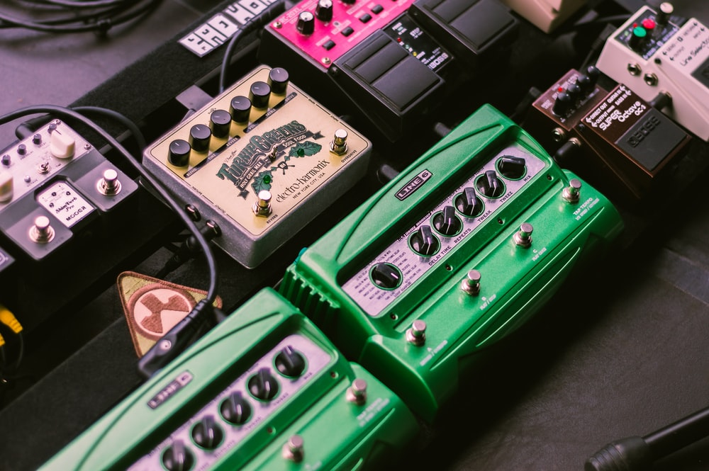 black and green effects pedals on black surface