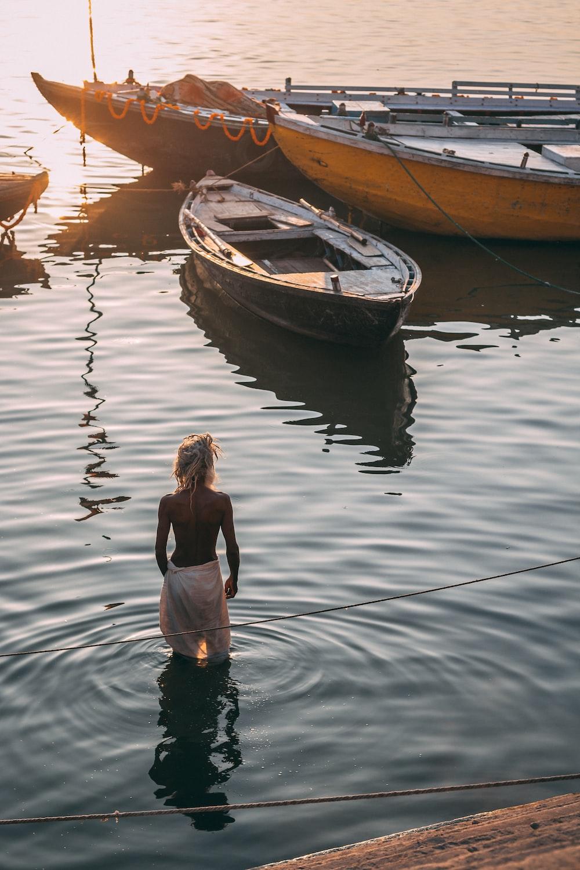 man wearing white bottoms in water near brown wooden canoe