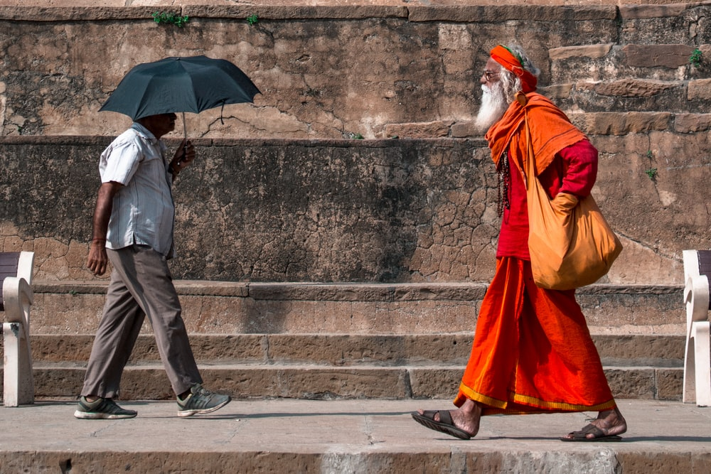 man walking beside man holding umbrella