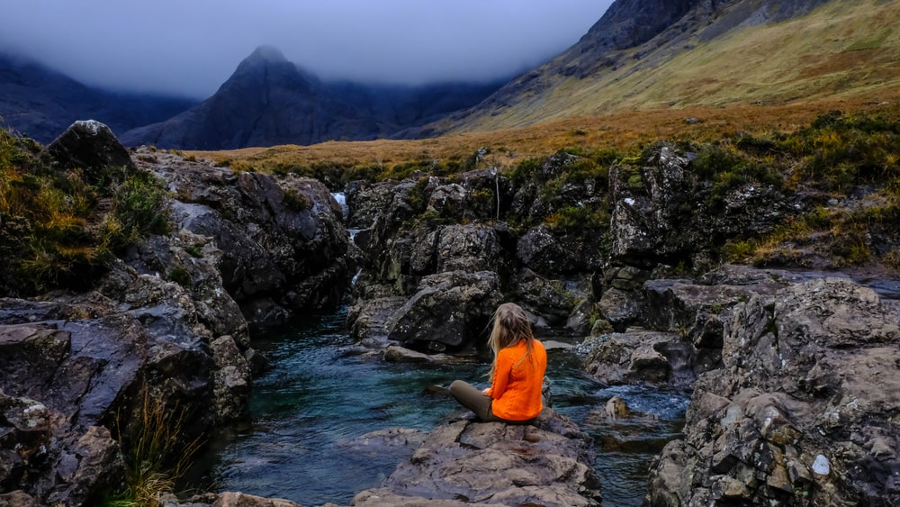 woman sitting on rock surrounded by water
