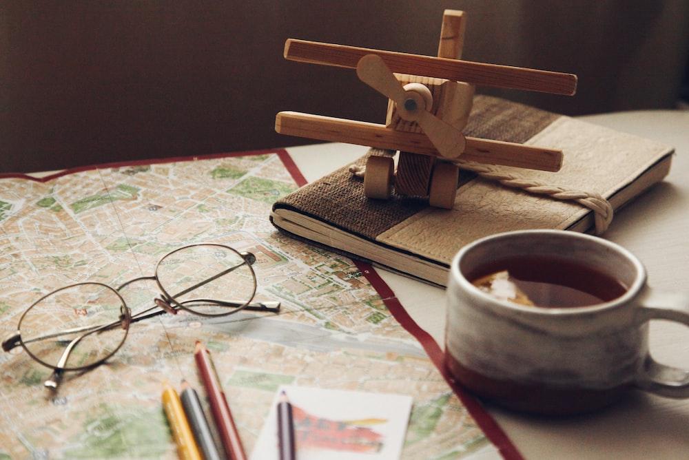 brown wooden biplane miniature on brown book
