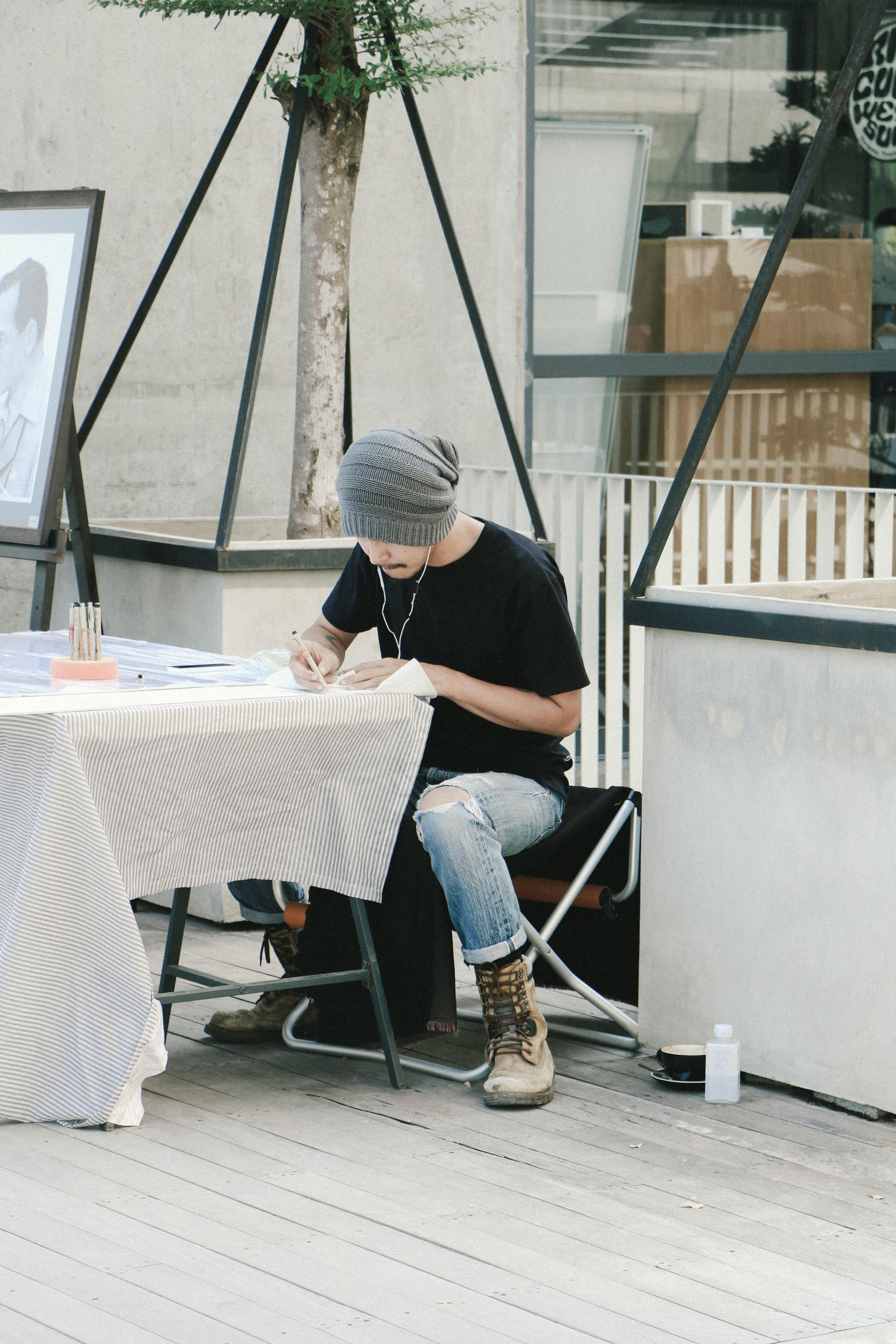 man writing on white printer paper
