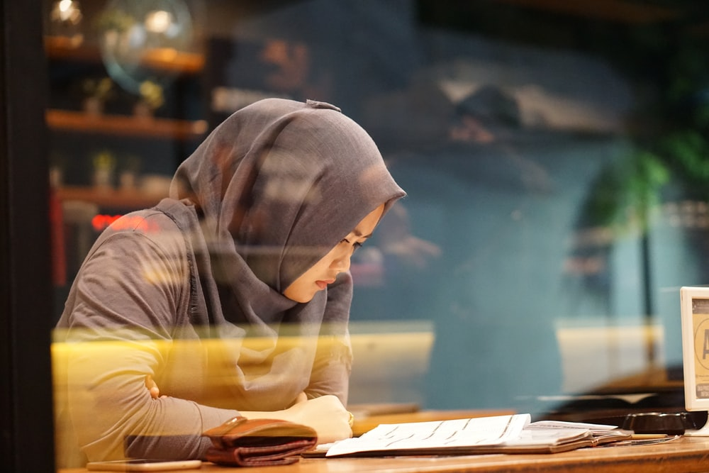 woman in gray traditional dress reading book