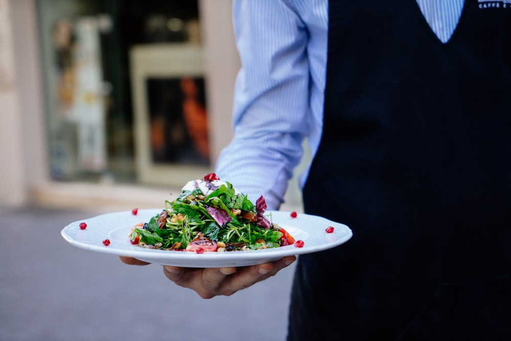 person holding a plate of salad