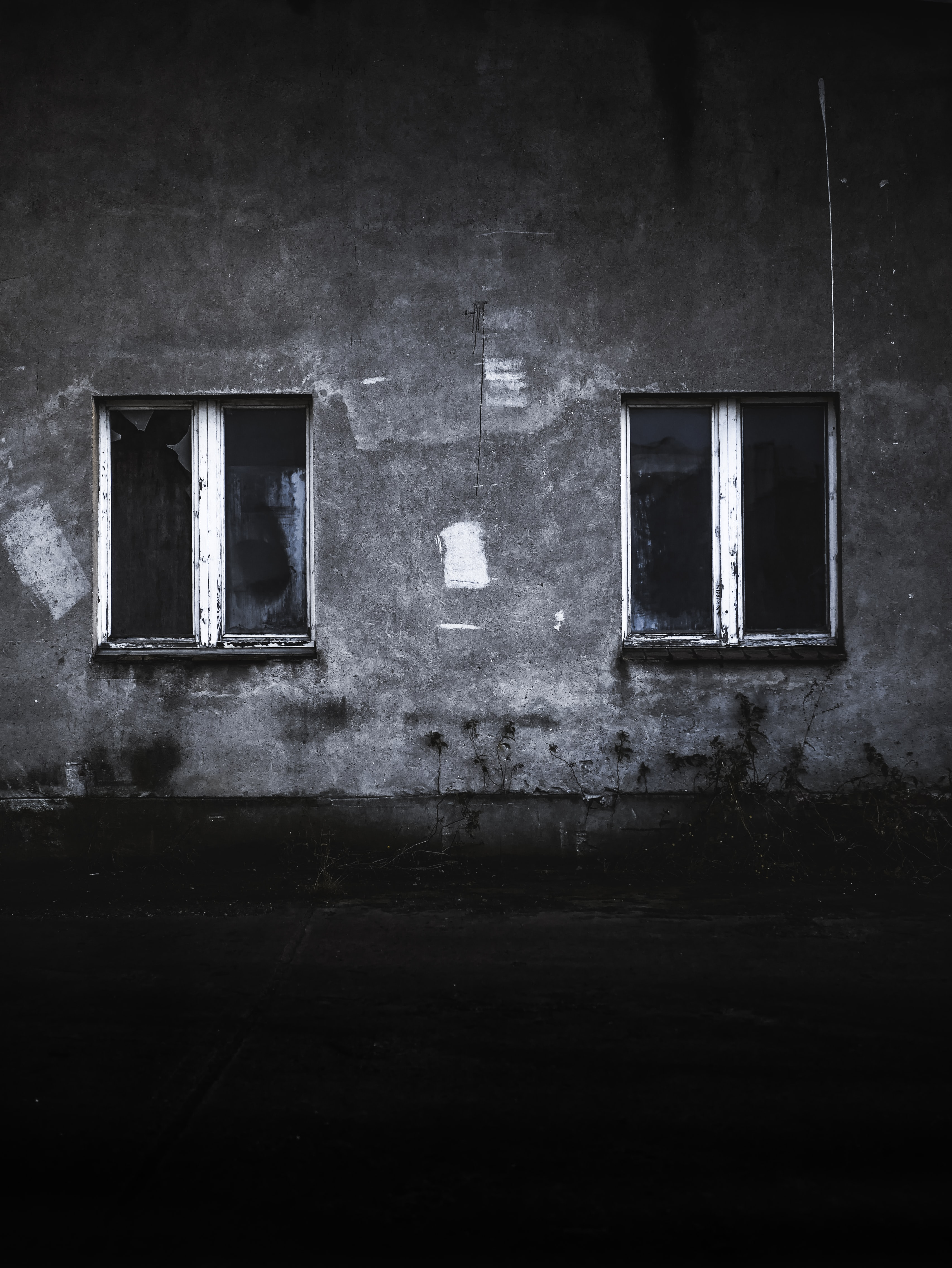grayscale photo of concrete house with two windows