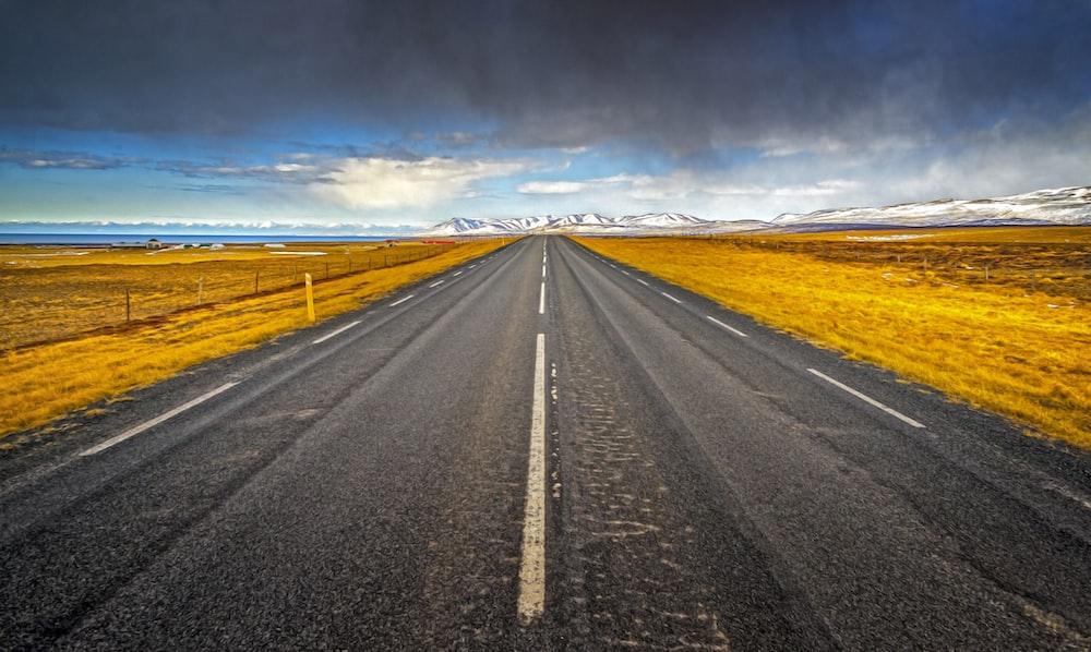 concrete road beside brown grass field