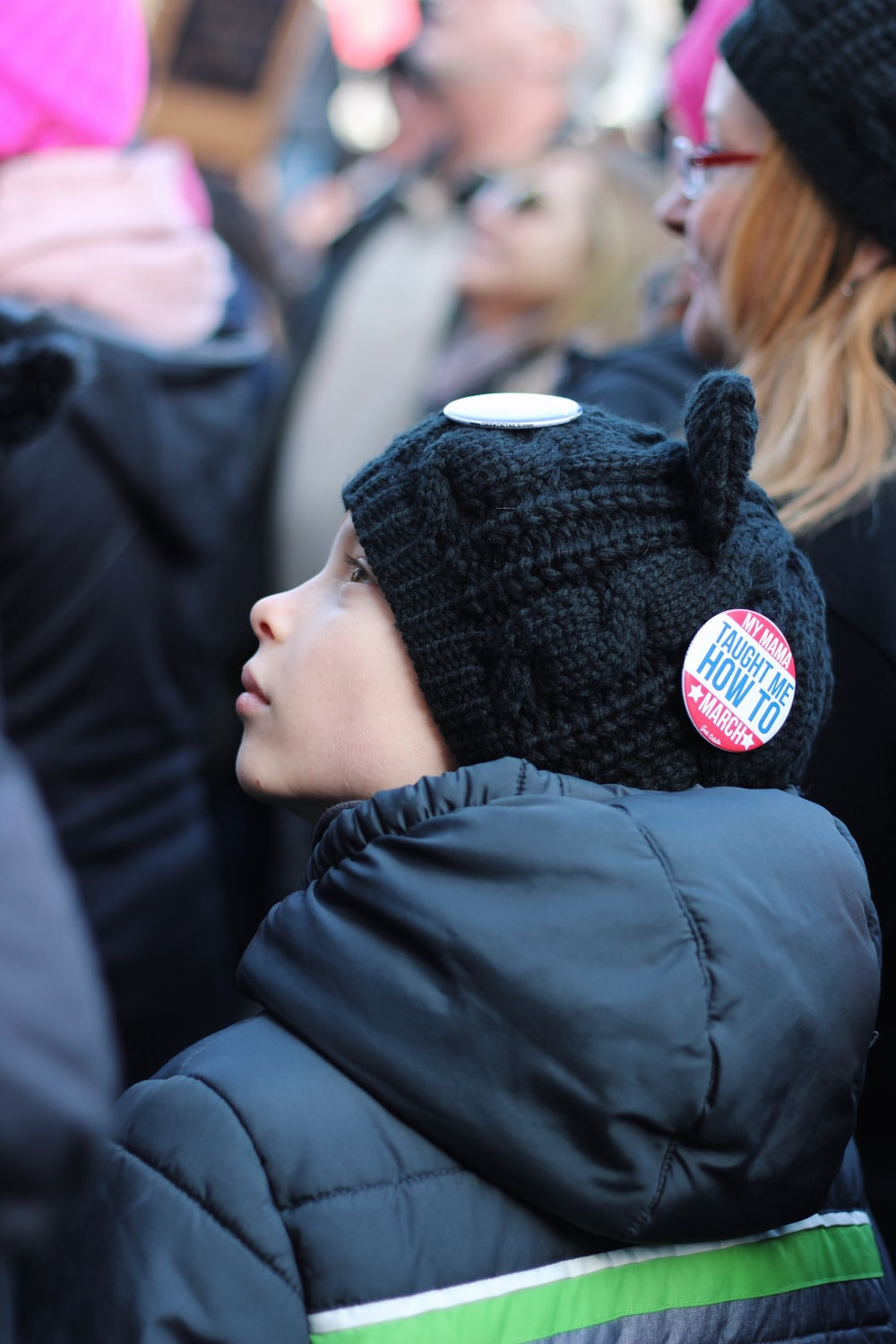 close up photo of boy's back sitting looking to the left wearing knit cap and hooded jacket