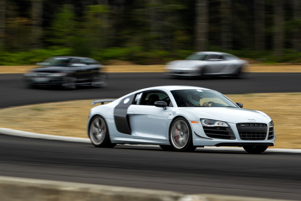 white Audi R8 driving on gray road
