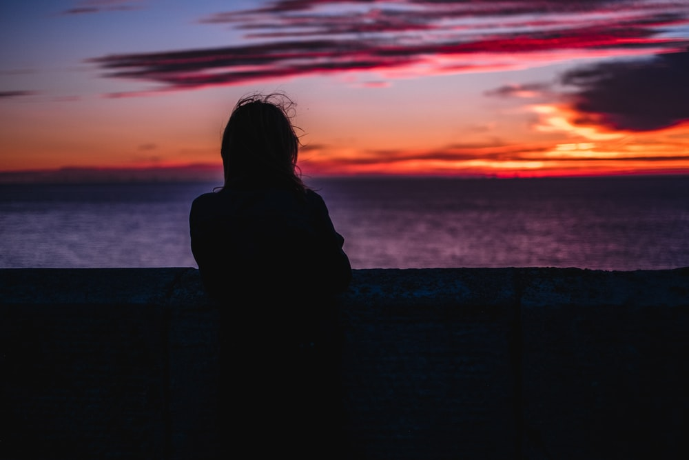 silhouette photo of person standing while looking at the ocean during golden hour
