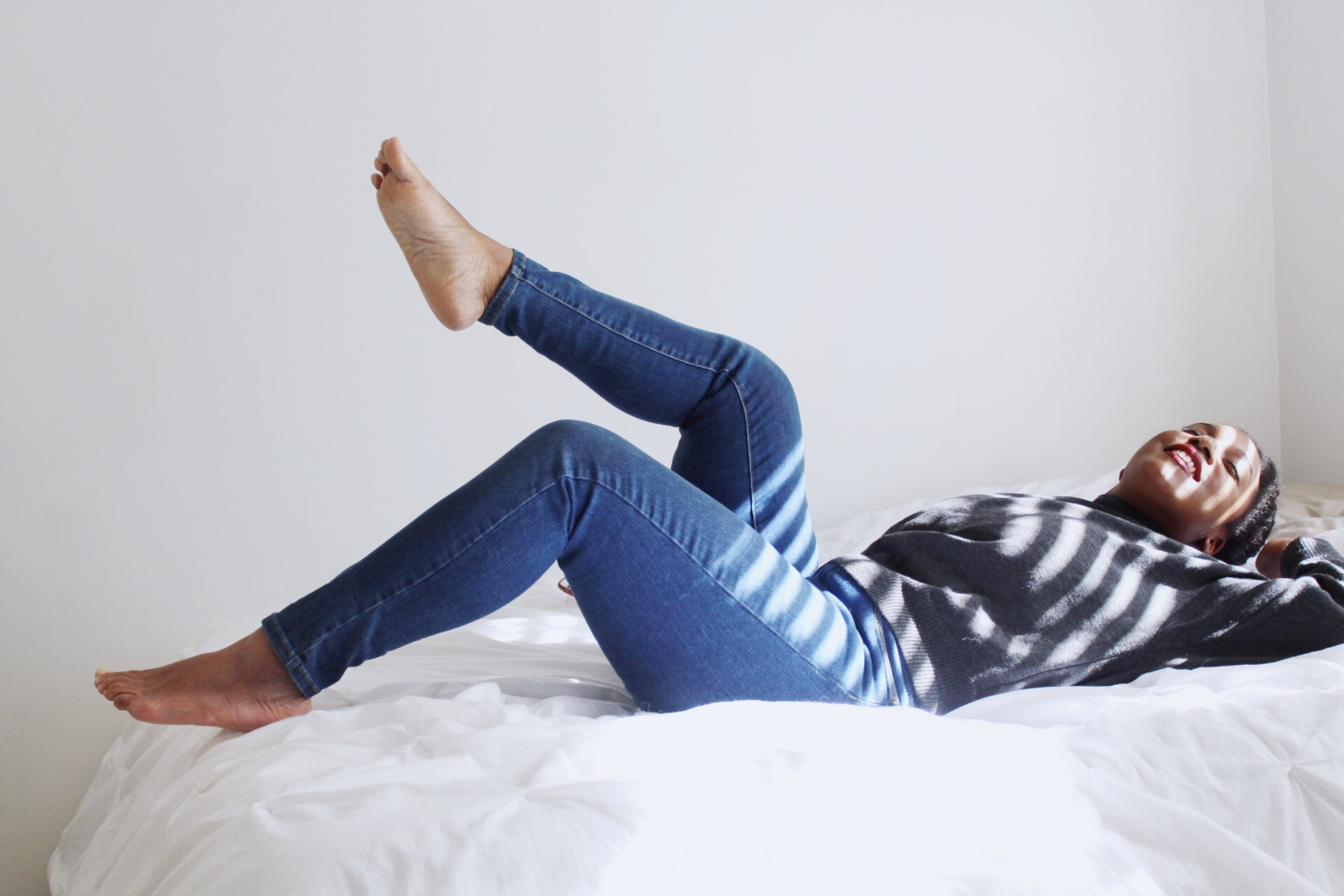 woman laying on white bed
