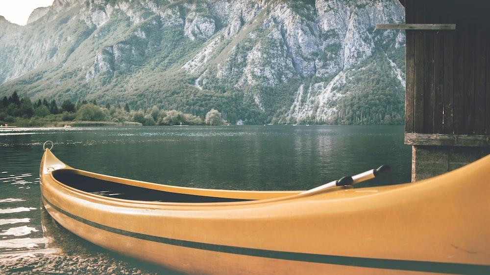 photo of orange kayak on body of water