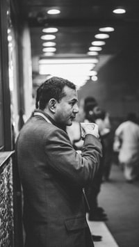 grayscale photo of man drinking on plastic cup