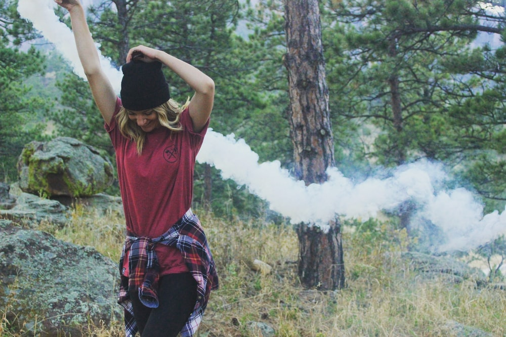 woman raising arms holding white smoke bomb standing beside rock surrounded with trees at daytime