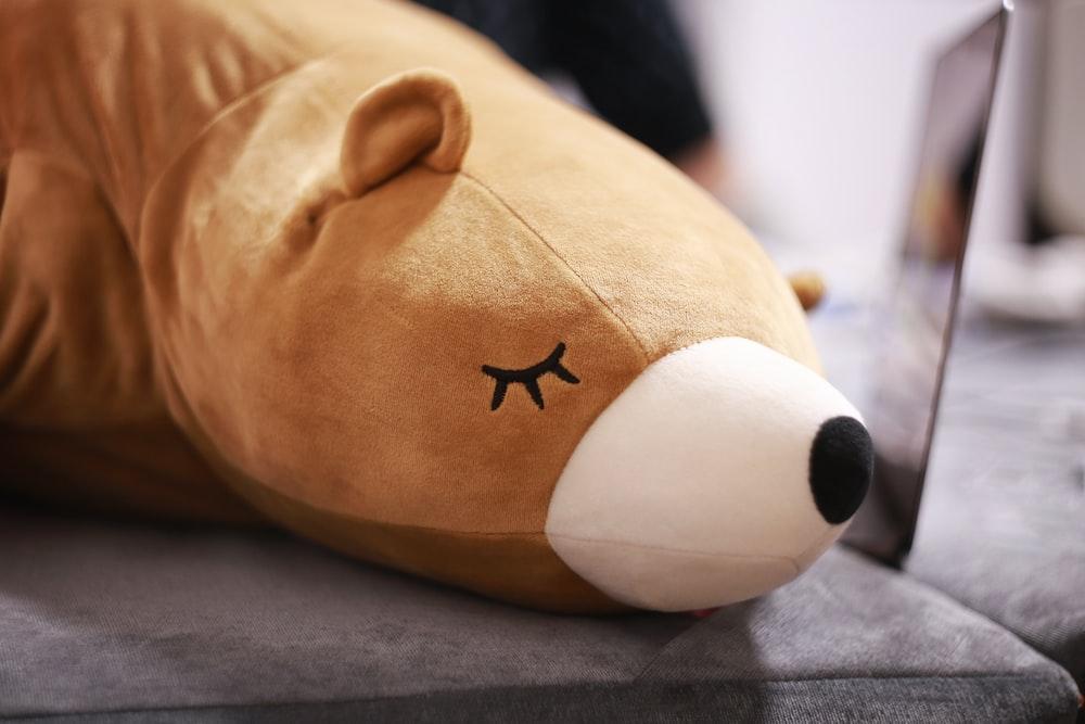 brown bear plush toy laying on brown cloth