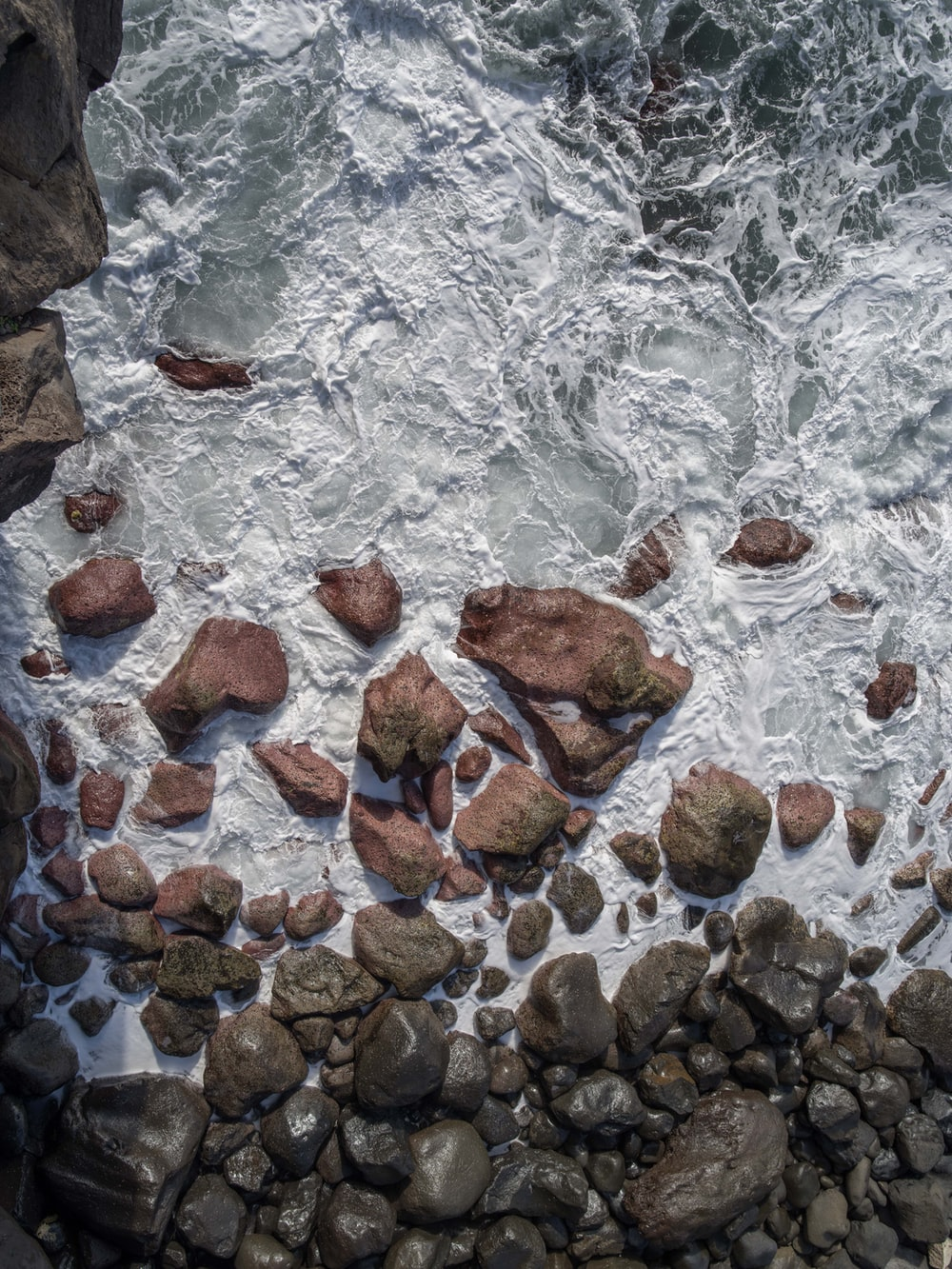 aerial view of rocks on body of water