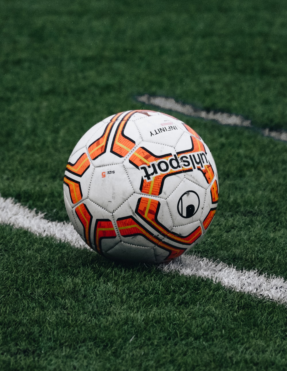 red and orange soccer ball on green grass field