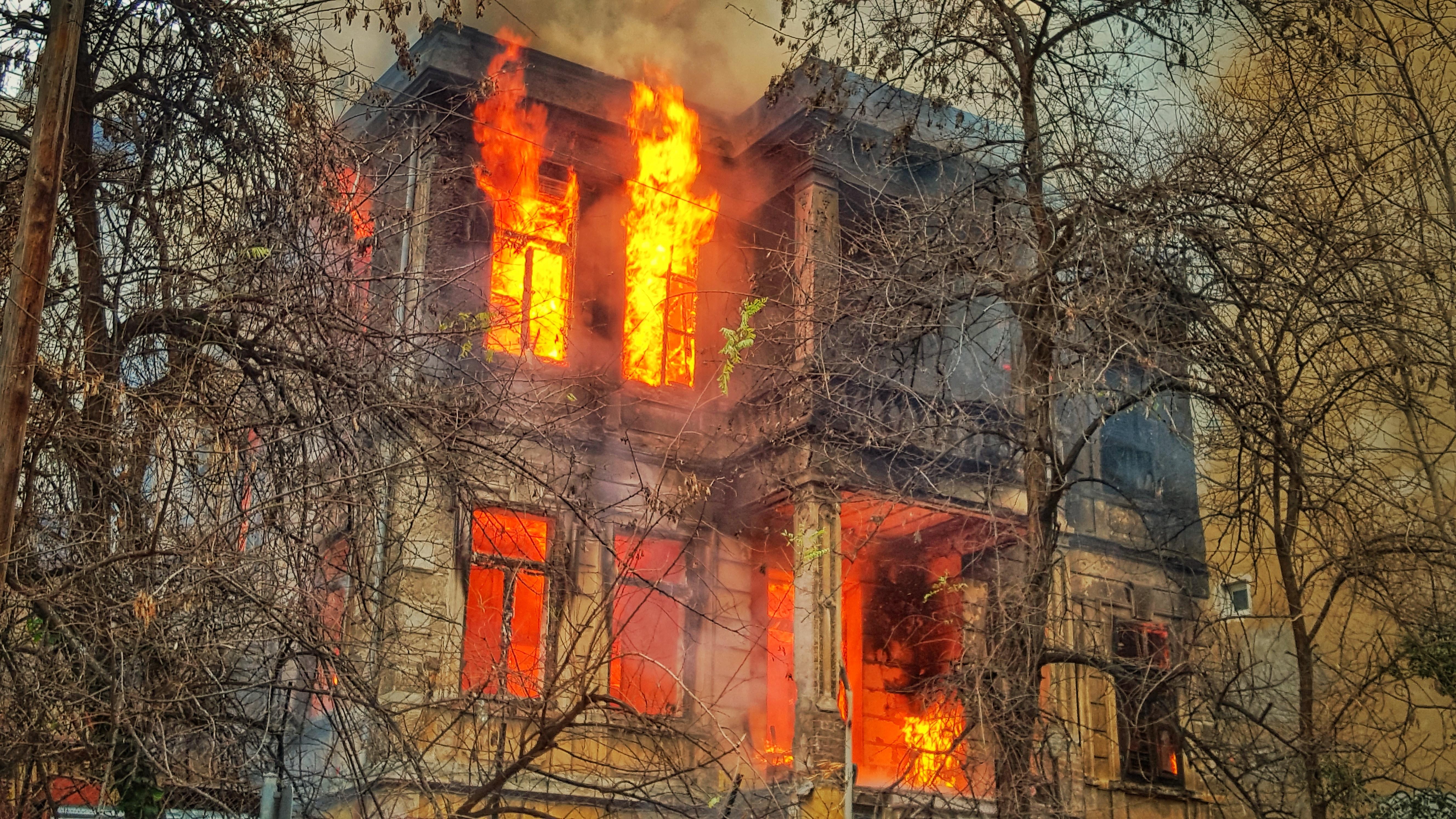 photo of burning house near trees