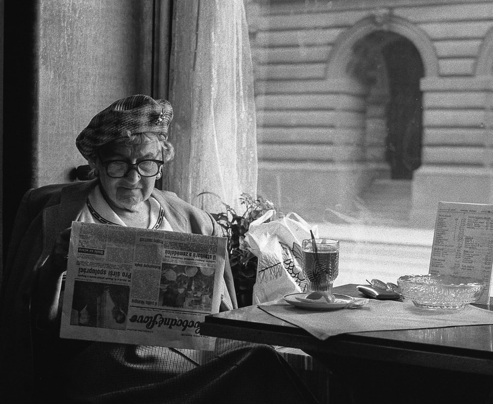 grayscale photo of woman sitting while reading newspaper