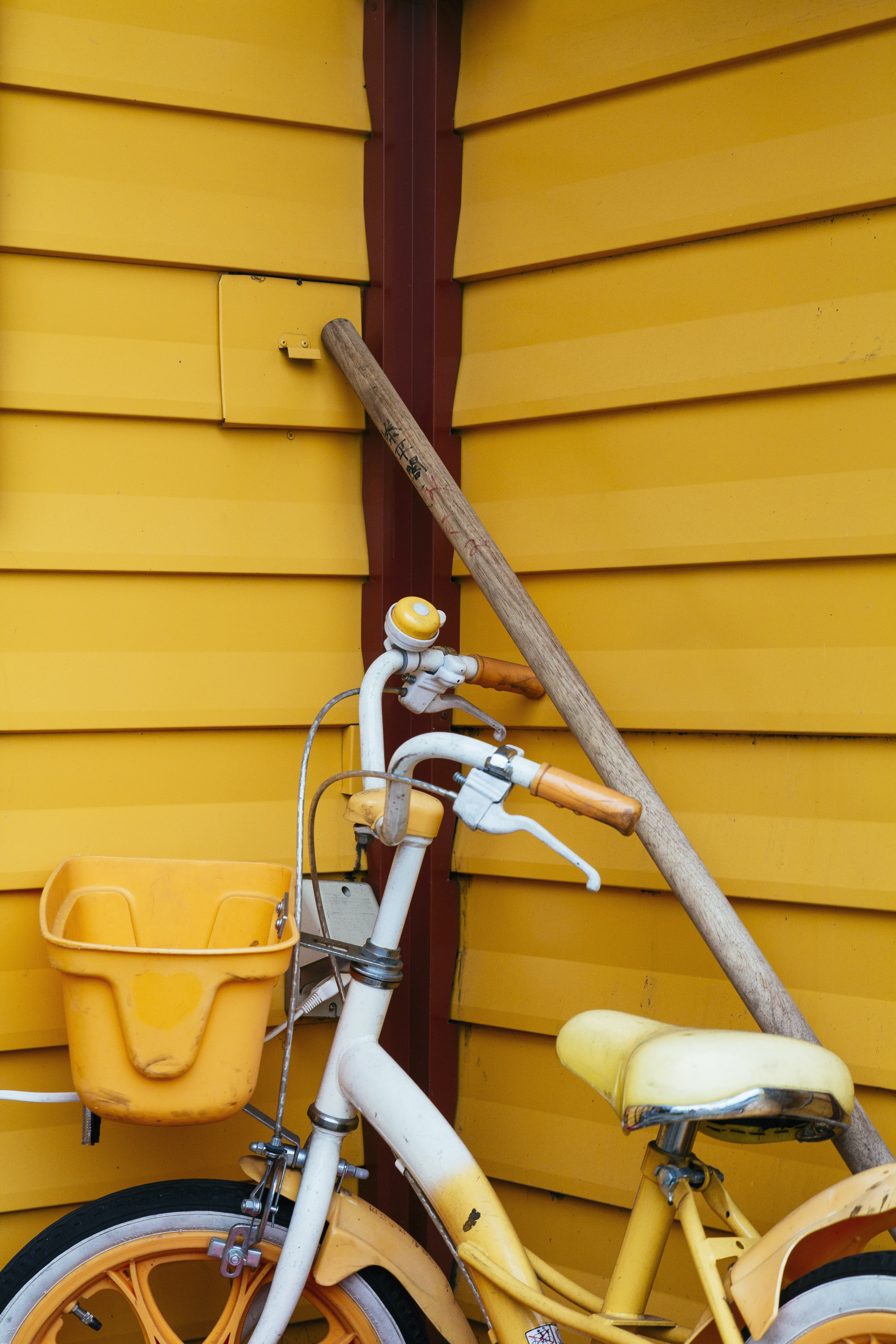 white and yellow bicycle beside brown wooden pole