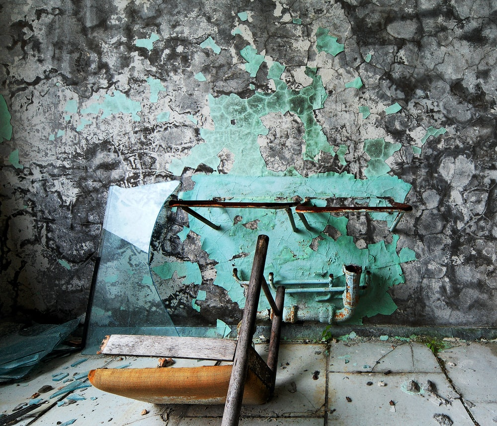 low-angle photography of broken chair near wall