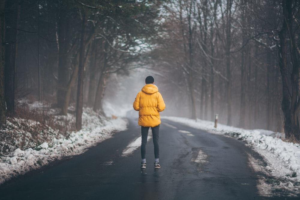 person wearing yellow jacket standing on road