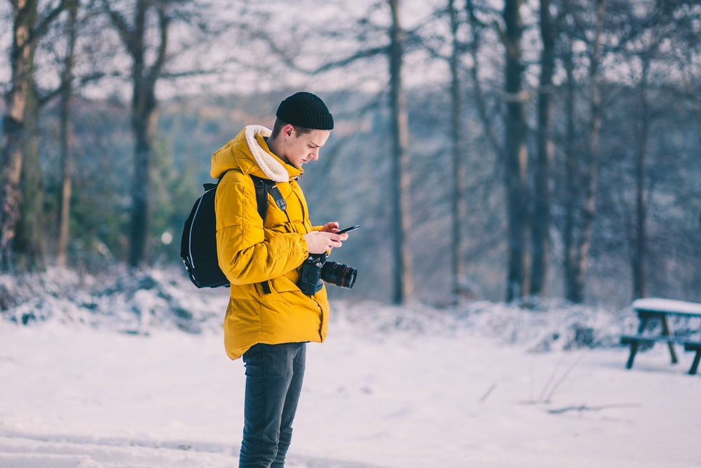 man in brown jacket using his smartphone