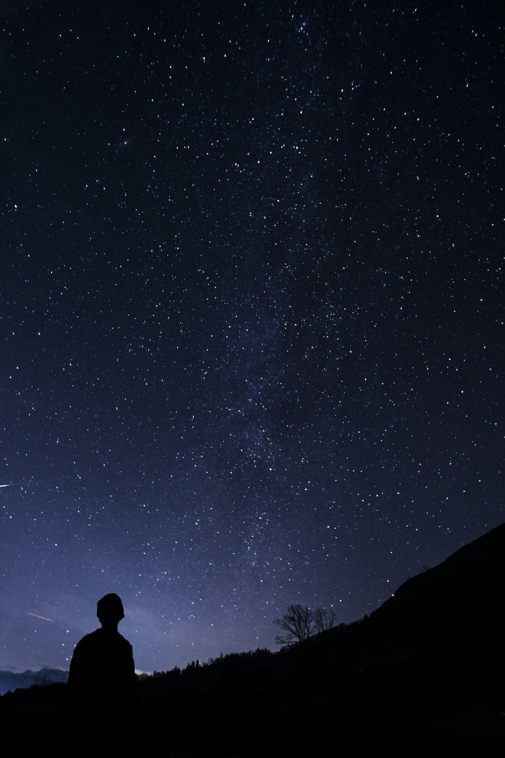 silhouette of man looking at milky way