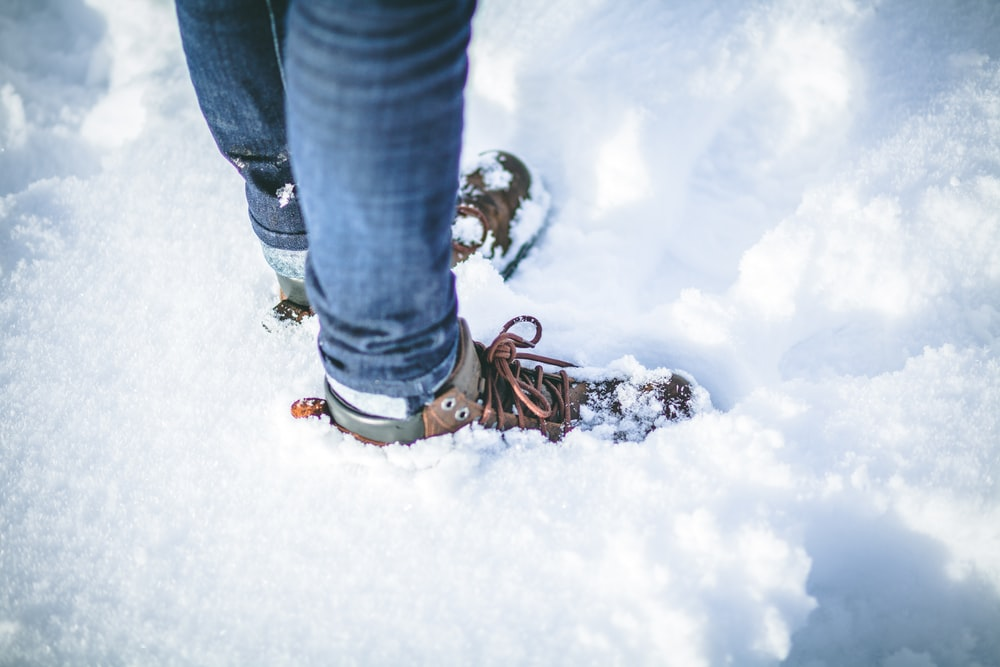 person wearing brown shoes on snow