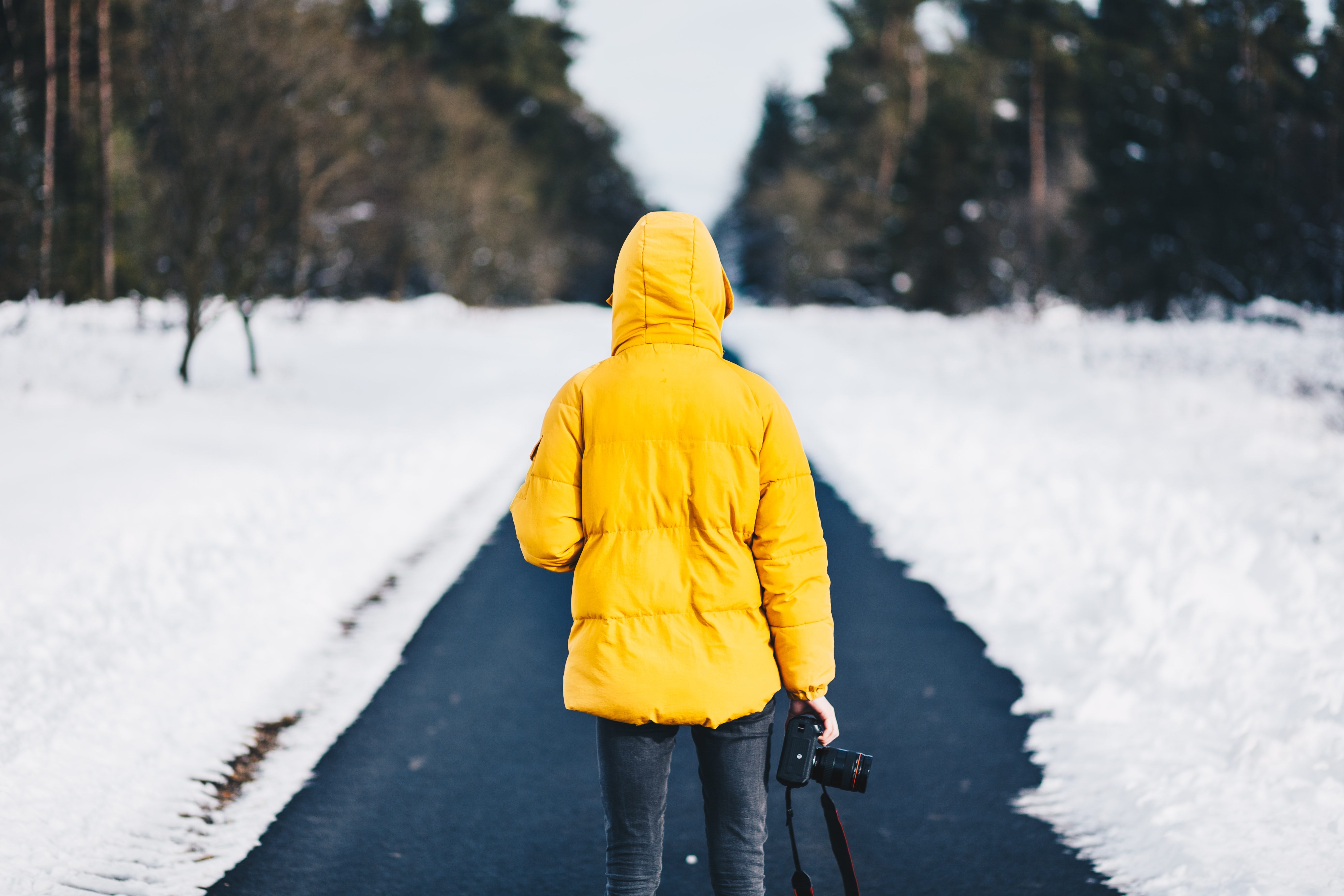person on yellow jacket standing between snow floors