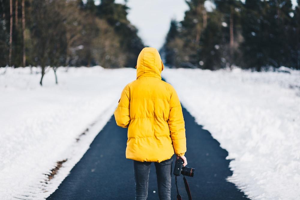 person on yellow jacket standing between snow floors