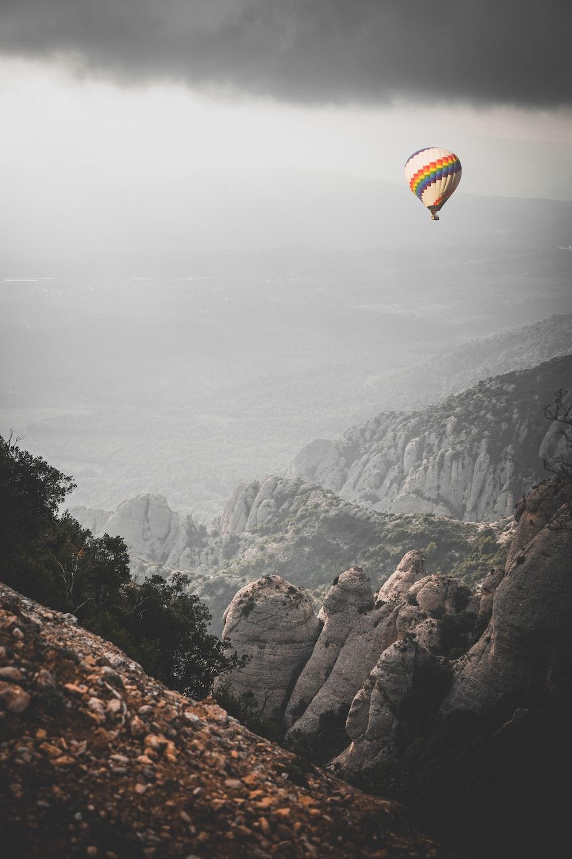 multicolored hot air balloon near mountains