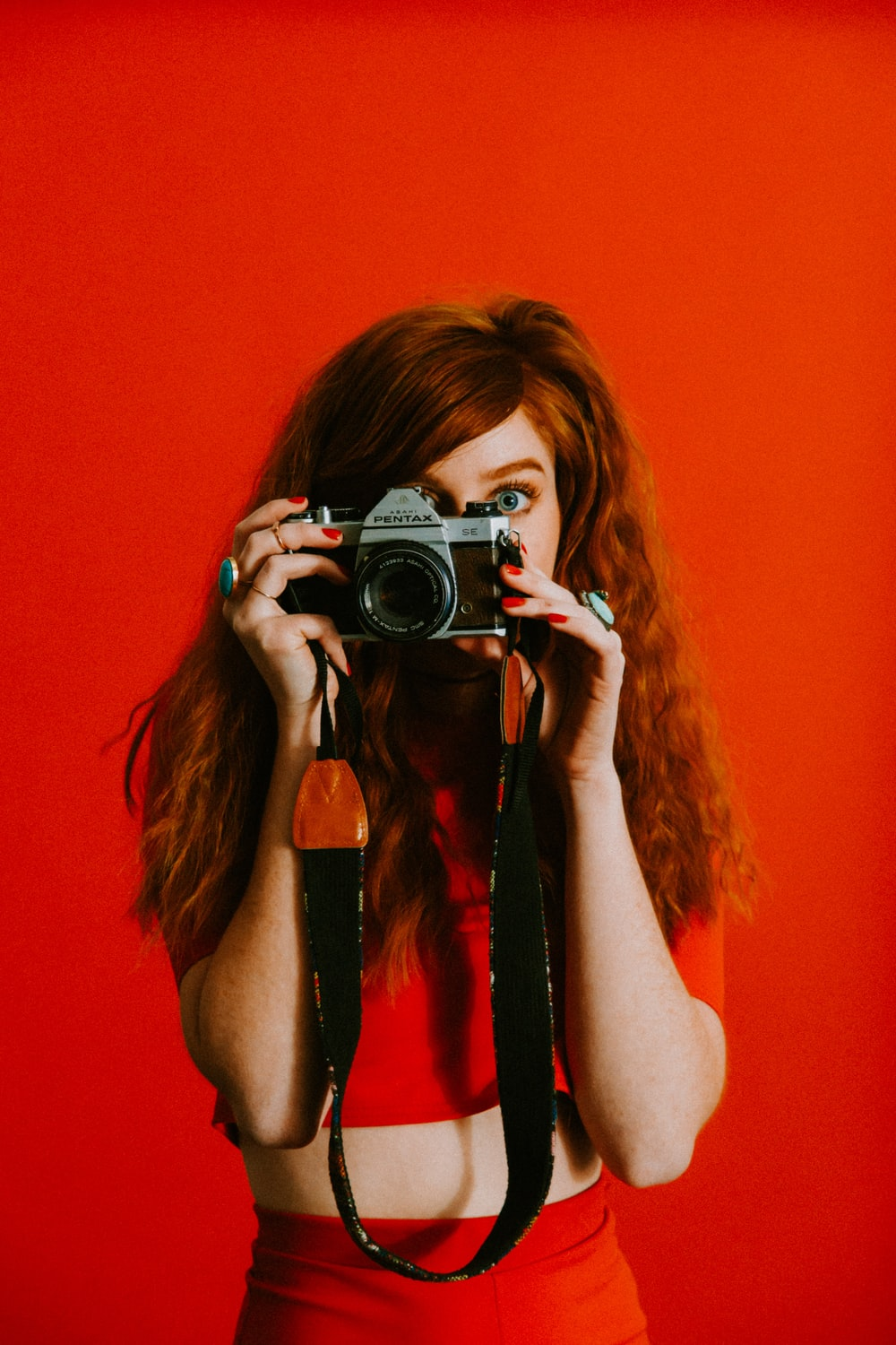 woman in red top and bottoms holding Pentax camera