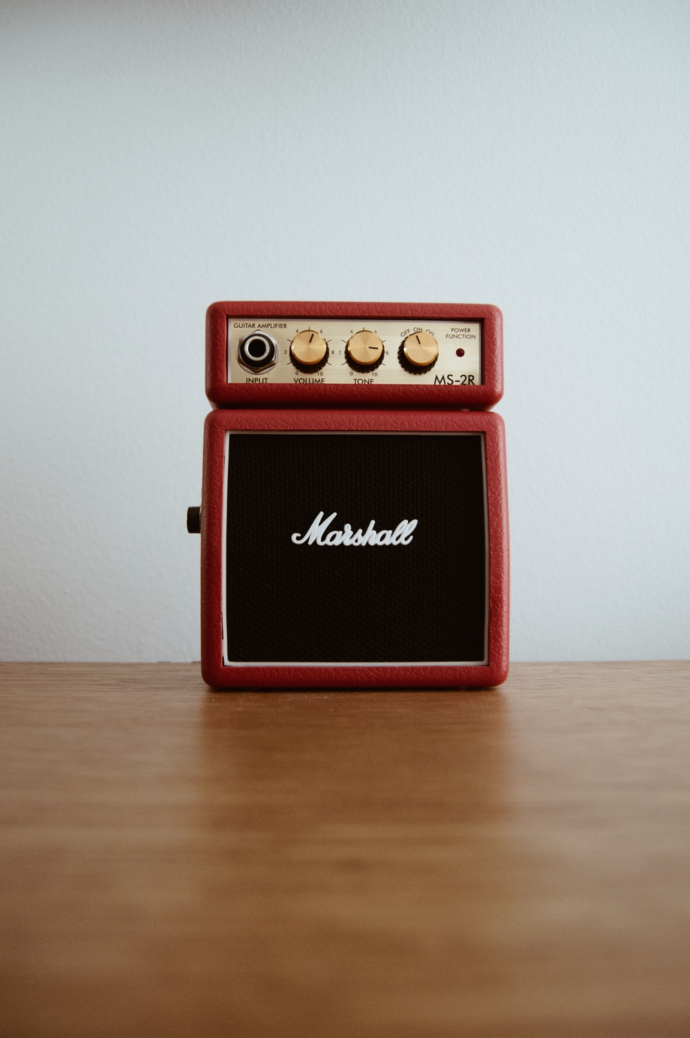 photo of brown Marshal guitar amplifier on brown board