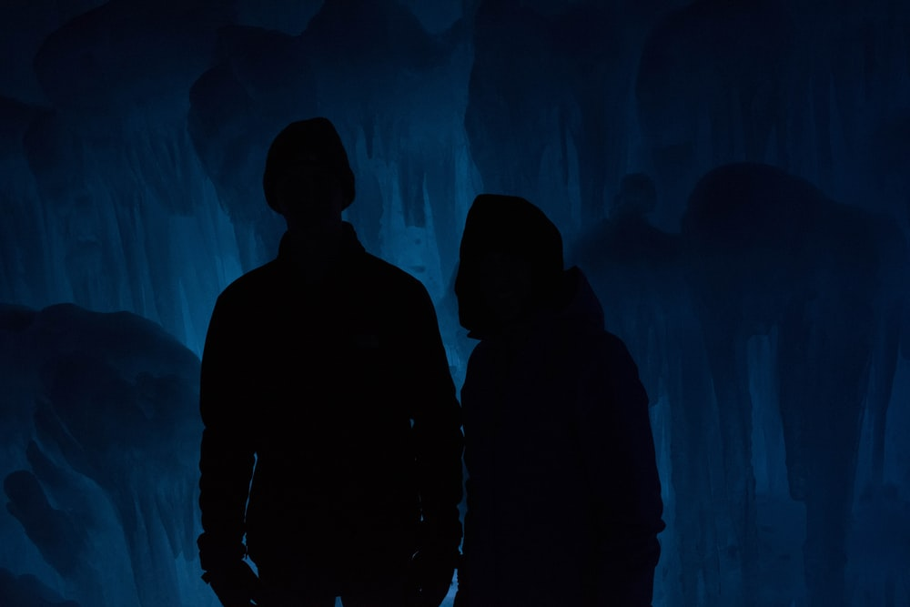 silhouette of man and woman inside cave