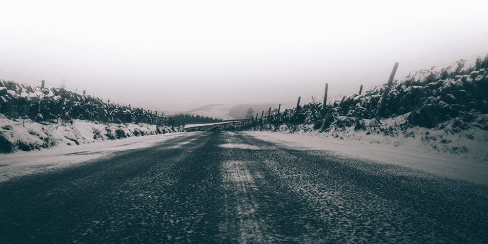 gray concrete road surrounded by snow