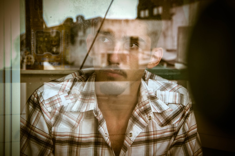 man looking out of window