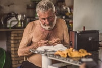 topless man sitting in front of table