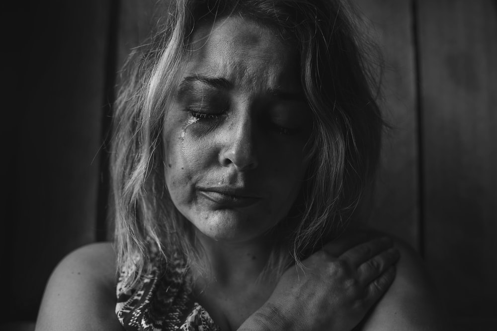 grayscale photo of woman crying holding her right chest